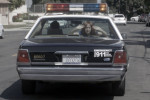 Young Raven (Jessica Bassuk) is being taken away in a police car